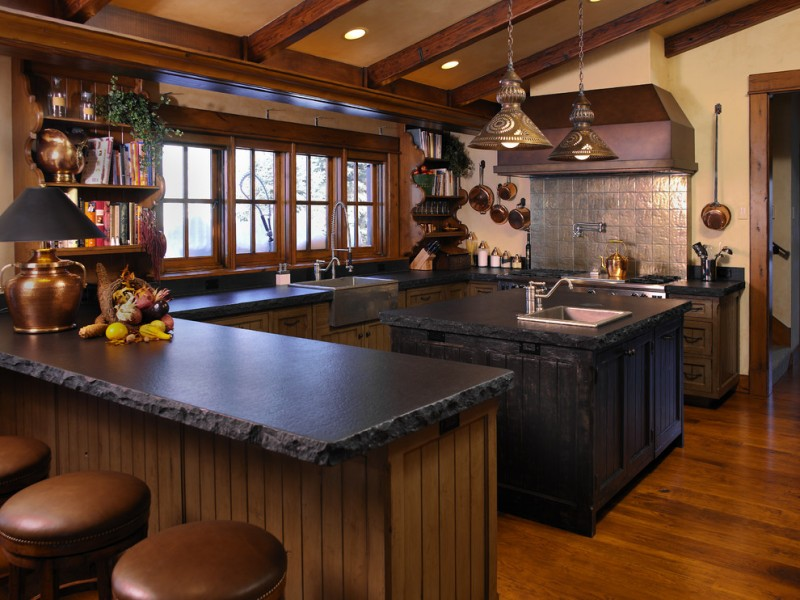 rustic gothic kitchen design soapstone L shaped countertop black hardwood kitchen island dark farmhouse sink and faucet dark brown rounded bar stools dark grey tile backsplash