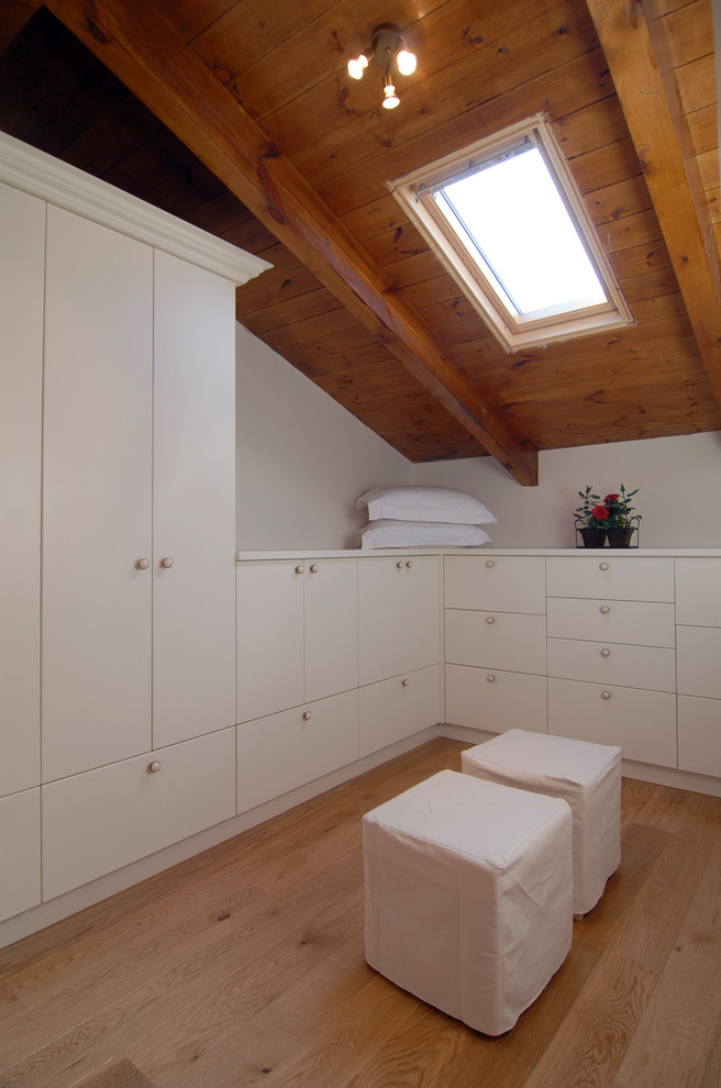 simple contemporary walk in closet with skylight hardwood slabs for roofs L shape white cabinets two ottoman chairs with white slipcovers and light tone wooden floors