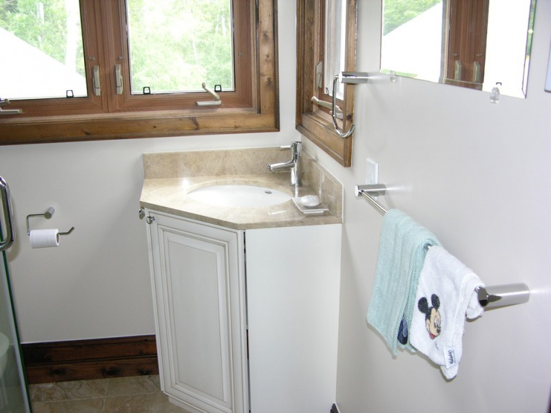 single corner bathroom vanity with cream marble countertop and white recessed sink