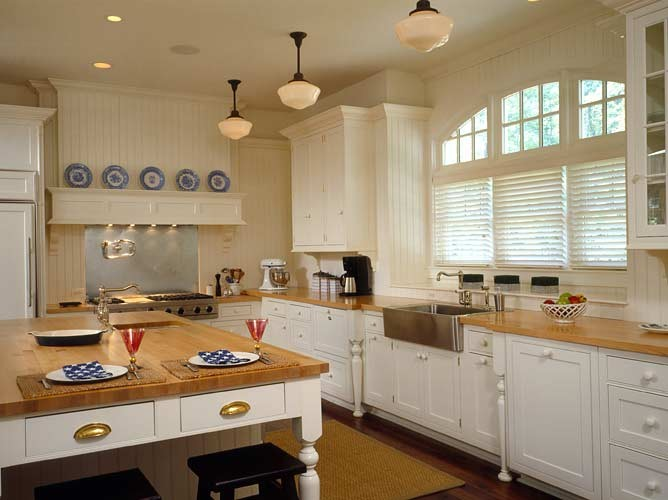 traditional kitchen design with coastal theme white cabinets wooden countertop wood top island medium tone wooden floors black finished bar stools stainless steel appliances