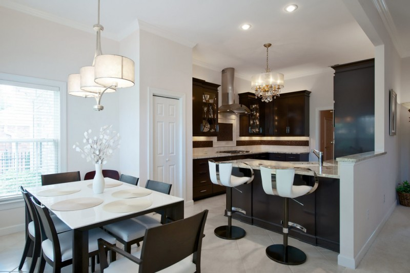 transitional kitchen dining room with white top square dining tables black wood dining chairs two modern stools white granite countertop dark finish cabinets luxurious chandeliers