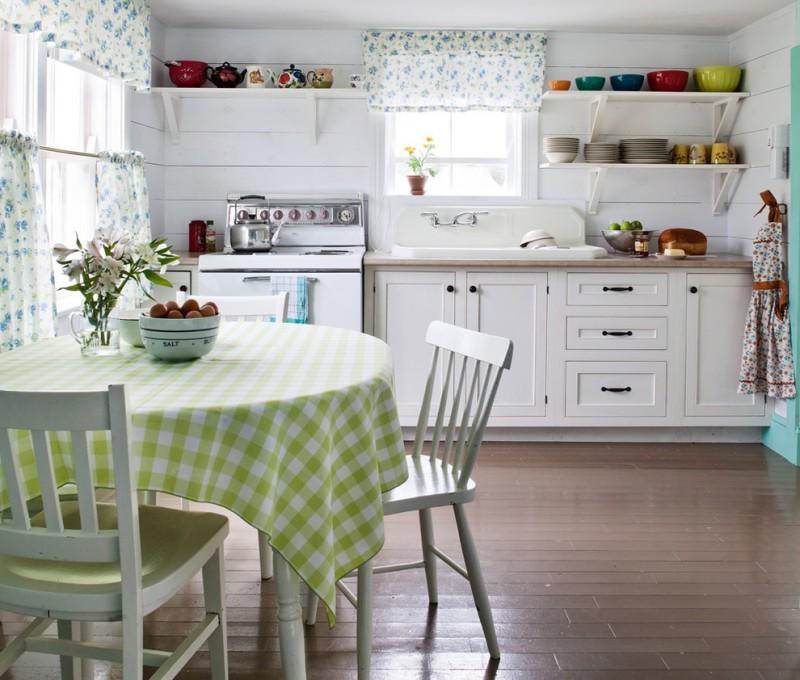 vintage themed kitchen design round dining table with gren white table cloth simple white dining chairs pure white kitchen cabinets floating white shelves for dishware