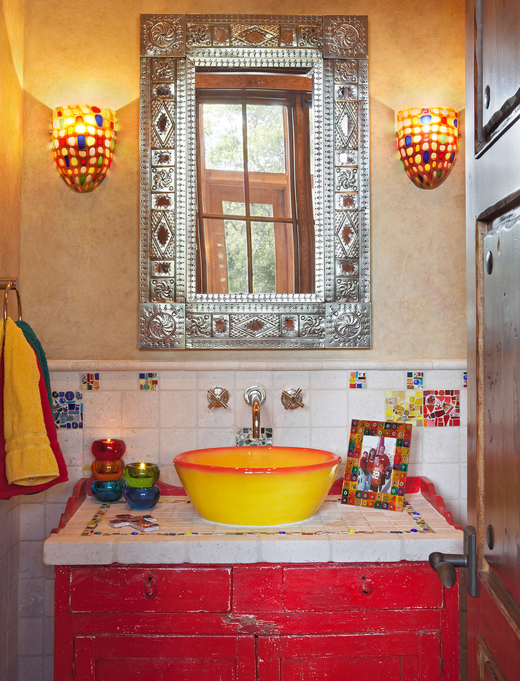 vintage vanity in shabby red and hand crafted tiles on top bright yellow basin and textured metal frame mirror a couple of wall lampswith mosaic shades