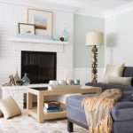 White Brick Fireplace In A Beach Themed Family Room Blue Navy Sofa Light Cream Center Table Abstract Paintings