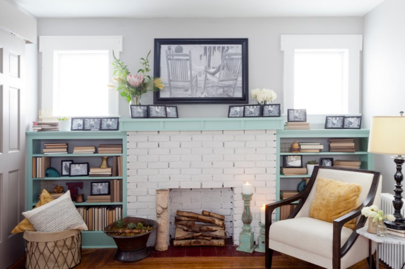 white brick fireplace installation with light blue mantel and book shelves a white armchair with yellow accent pillow