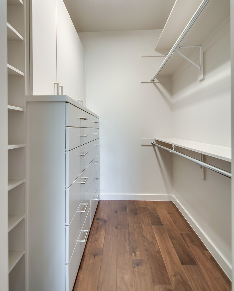 white minimalist walk in closet idea medium height drawer system white open shelves upper & lower chrome hang sections medium tone hardwood floors