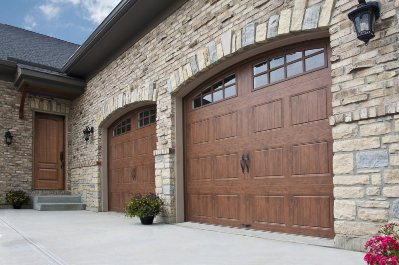 woodgrain veneer garage door with dark metal handles