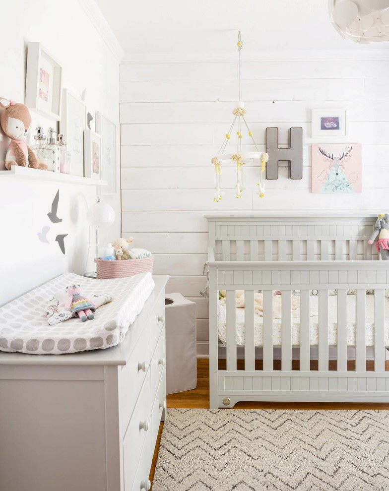 airy nursery idea white crib white changing table white area rug with grey modern patterns medium toned wood floors white siding walls
