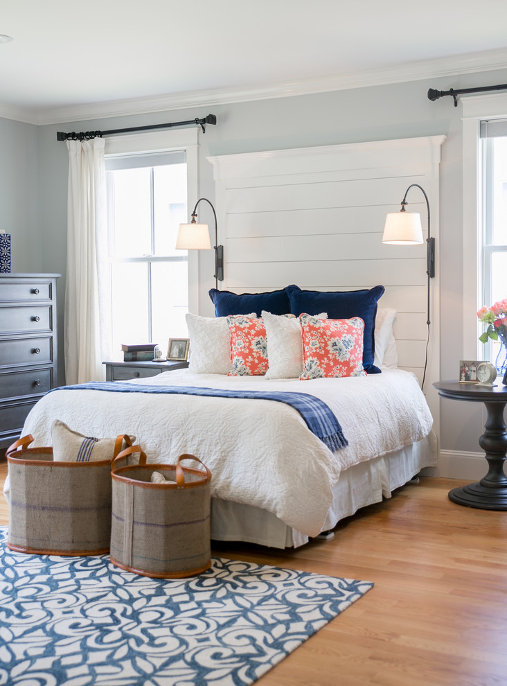 beach style bedroom idea in basement traditional bed frame with higher white headboard ivory pillows white window curtains light grey walls medium toned wood floors