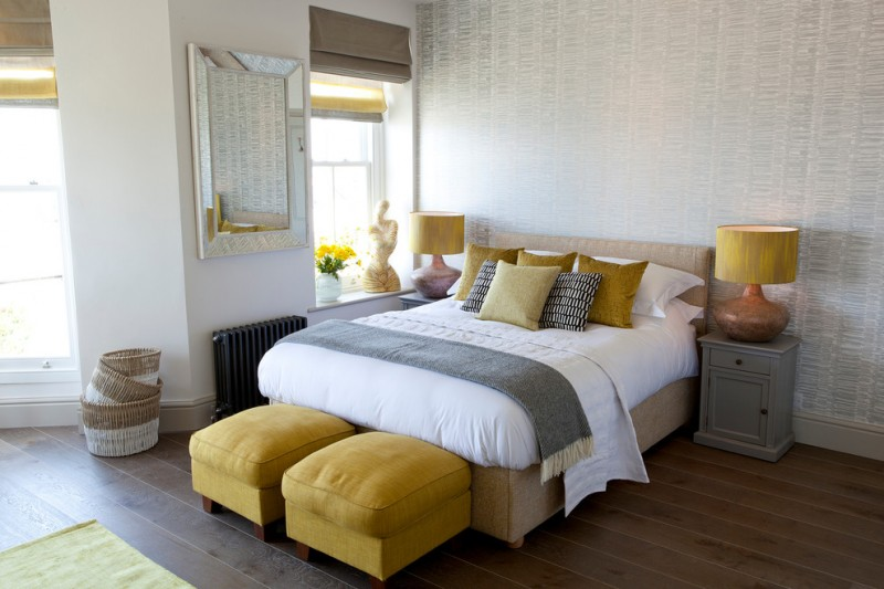 beach style bedroom idea white bedding treatment with mustard pillows grey bedside tables a couple of mustard ottoman chairs medium toned wood floors texture white walls