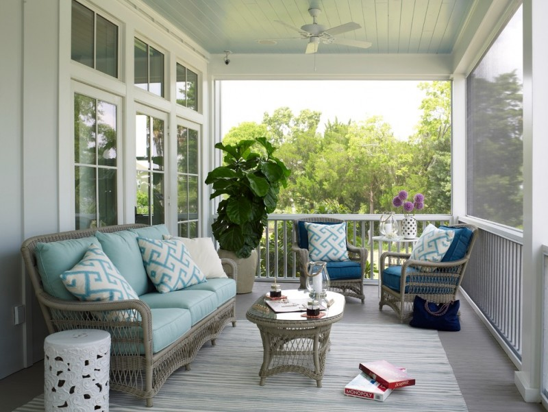 beach style porch in grey light grey wood board floors grey seating units with deep and light blue seating pads