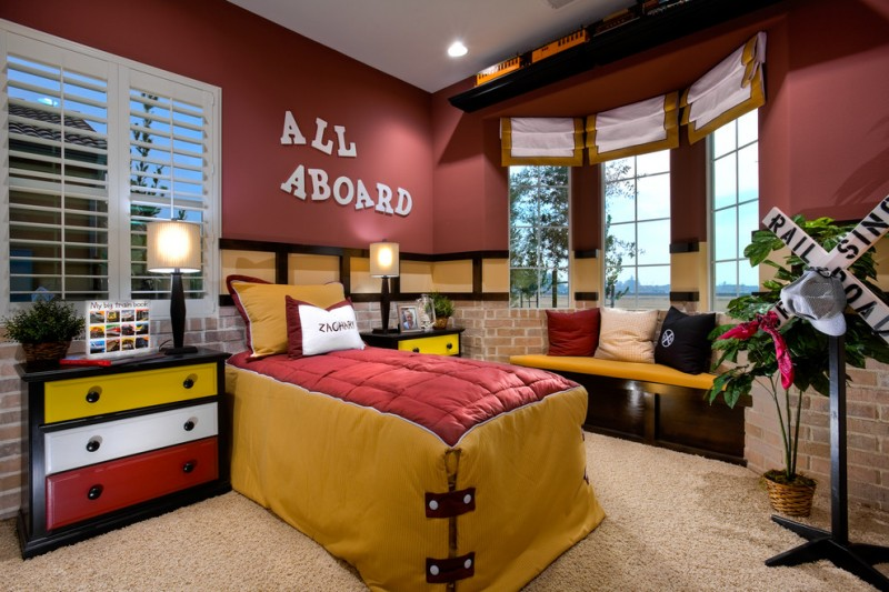 boy's room idea maroon walls glass windows with white shutters glass windows with rolled up draperies bold red mustard bed comforter corner bench under windows with dark toned wood base