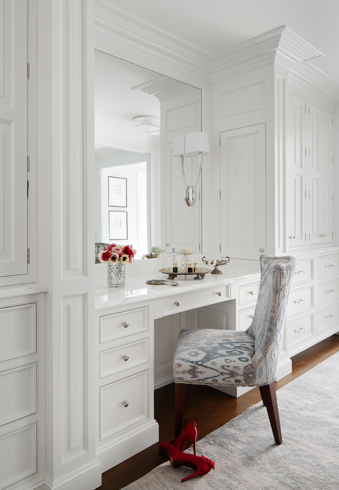 clean white traditional walk in closet with recessed dressing table frameless vanity mirror soft patterned vanity chair light grey carpet dark toned wood floors