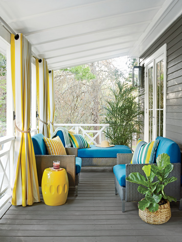 coastal front porch idea grey seats with blue covered foams blue yellow stripped throw pillows yellow side table grey wood board floors