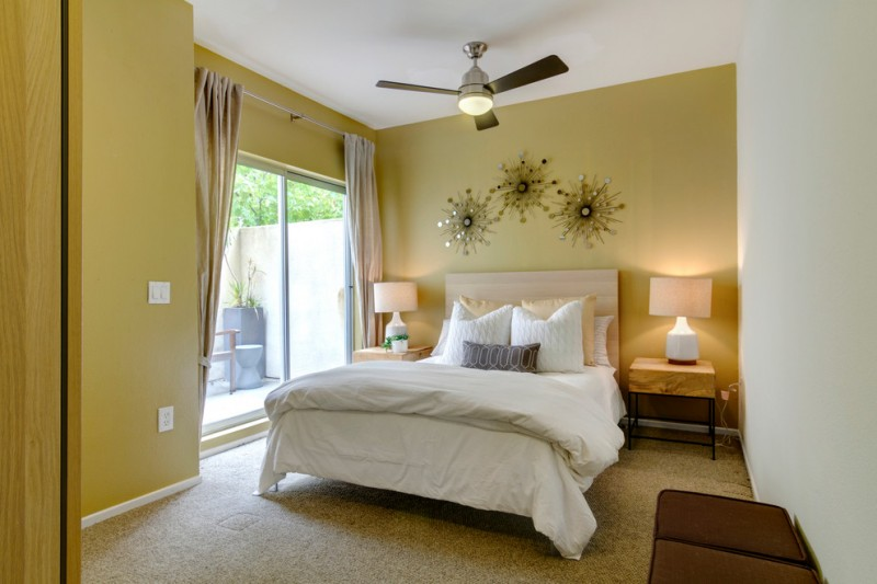 contemporary bedroom yellow mustard walls metal wall arts dark ceiling fan beige area rug wood bedside tables with table lamps