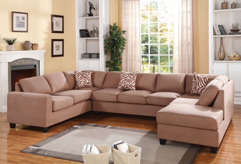 contemporary sectional in u shape and bold peach color accent pillows grey area rug medium toned wood floors