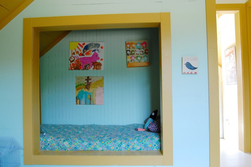 farmhouse kids bedroom idea recessed bed space with yellow mustard frame bright blue walls with kids paintings