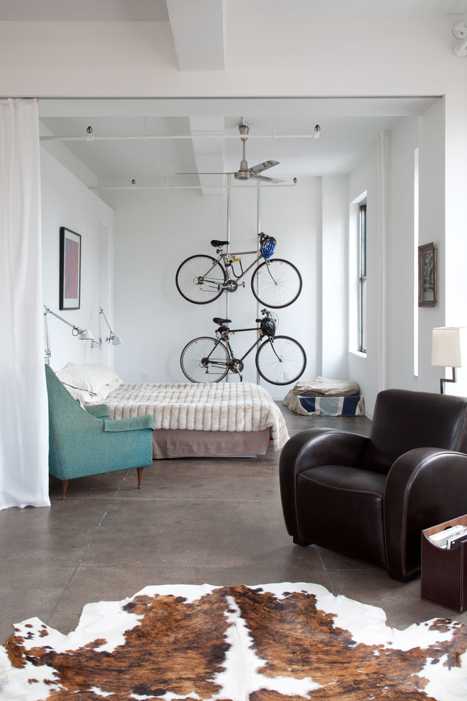 industrial bedroom idea a couple of hanging bike racks turquoise corner chair dark brown leather armchair cowhide area rug white walls