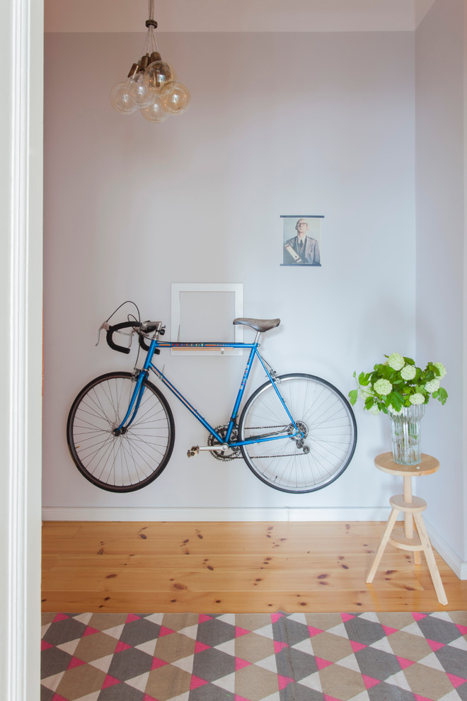 industrial hall idea wall mounted bike a group of lightbulbs pendant lamp round shape wood side table with clear glass flower vase medium toned wood floors