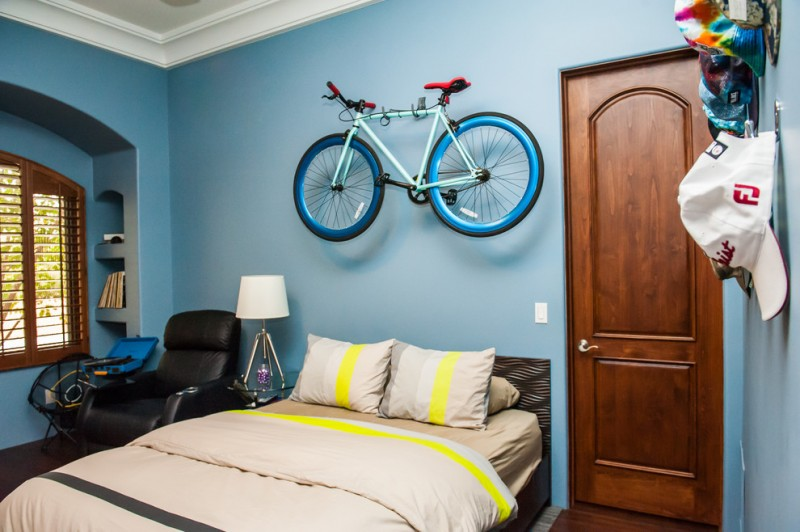 large & modern boys' room with dark wood floors and blue walls accented with blue turquoise hanging bike decor