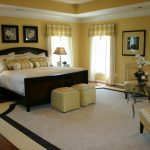 Light Mustard Walls White Transparent Draperies With Mustard Upper Window Skirts Dark Toned Wood Bed Frame With Headboard Gold Toned Chairs Dark Toned Wood Bedside Tables