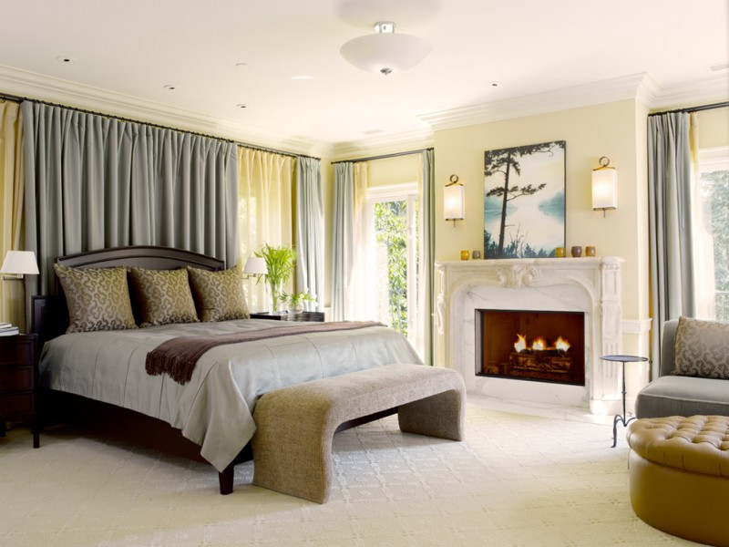 master bedroom idea soft mustard walls traditional white fireplace with crafted surrounds grey window draperies with light yellow inner draperies silver bed linen grey bed bench
