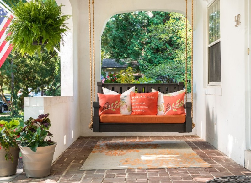 mediterranean style front porch idea dark grey porch swing with orange seating pad and orange accent pillows terracotta tiles floors