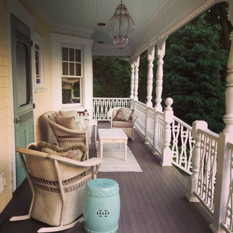 medium size victorian style front porch with rails and pillars craftsmenship chairs in soft color pale toned coffee table dark wood board floors classic glass pendant lamp