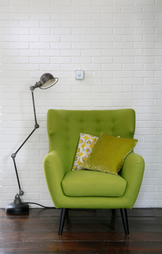 mid century living room white painted brick walls green vintage armchair with accent pillows vintage style floor lamp in black dark toned wood floors