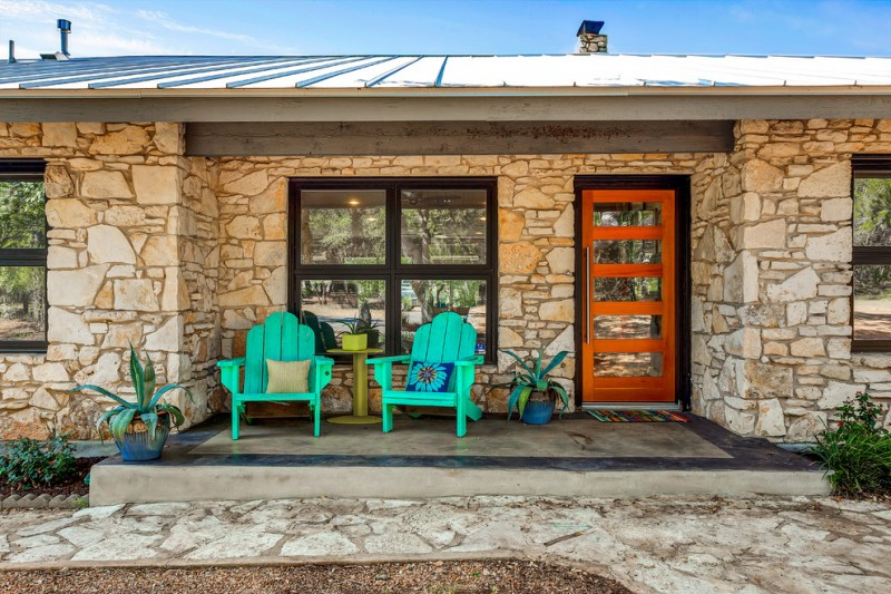 mid century modern porch idea a couple of turquoise chairs with accent pillows green side table natural stone exterior walls concrete floors wood color front door
