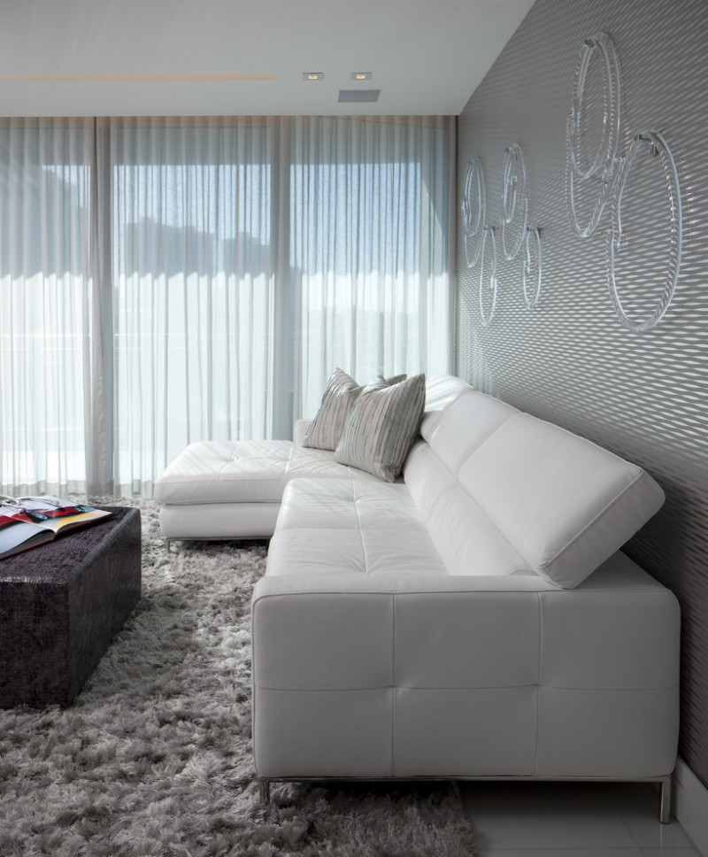 modern basement living room white window linen sheer silver walls glass ring wall decorations white leather sectional with silver accent pillows dark coffee table grey shagr rug