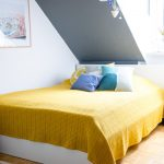 Modern Bedroom Idea With Grey Slanted Ceilings Mustard Bed Line Pop Colored Pillows
