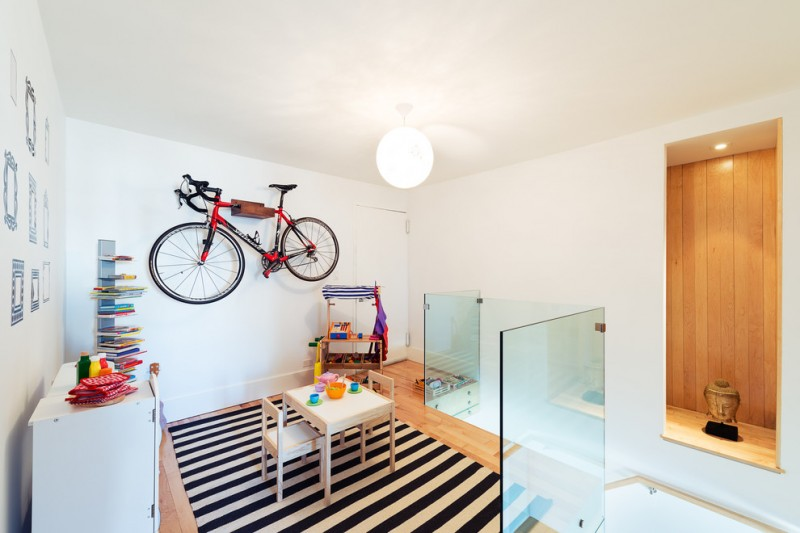 modern kid's playground with ornamental wall mounted bike white table and chairs white black stripes rug light toned wood floors stand bookshelves large central lightbulb in white