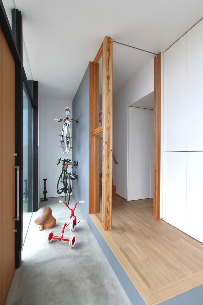 modern minimalist entry way concrete floors medium toned wood entrance door medium toned wood floors corner mini bike shed