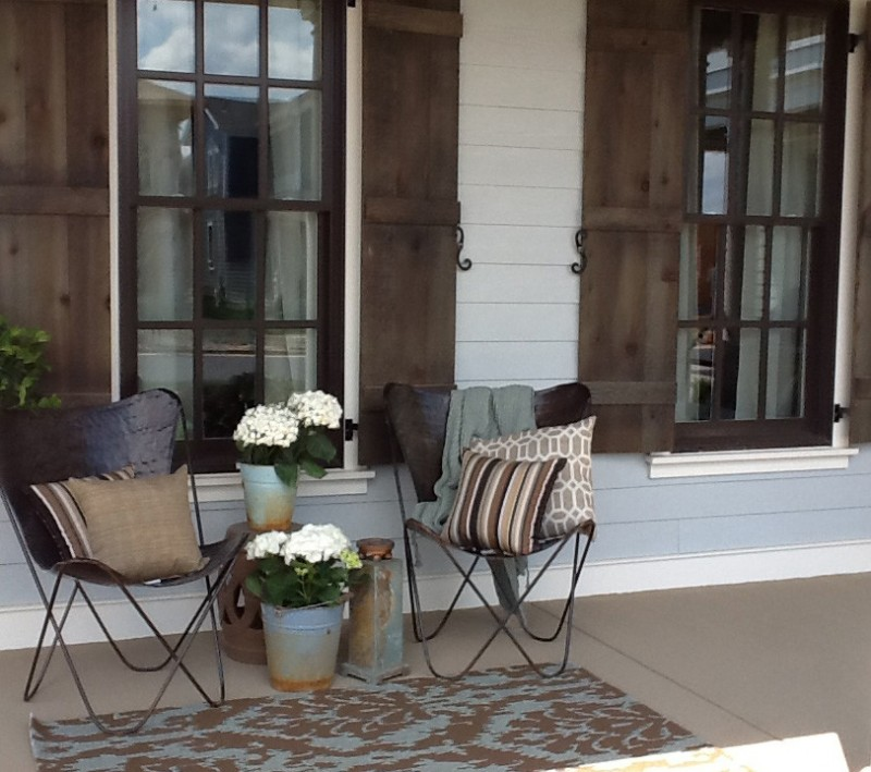 modern rustic front porch idea white ceramic exterior walls glass exterior windows with dark wood shutters hairpin chairs small sized rug