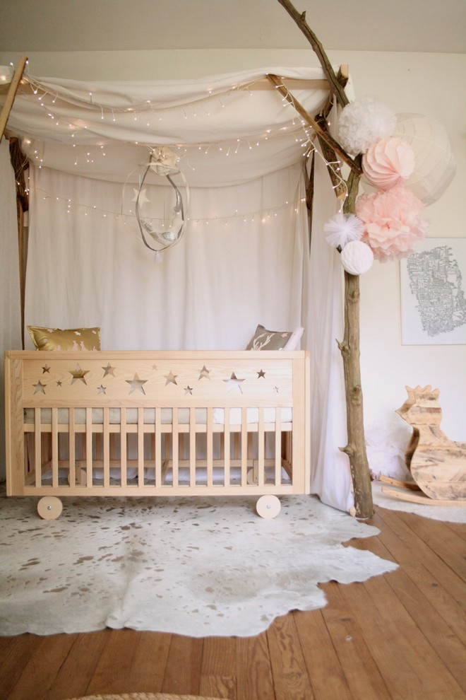 natural feel nursery idea medium toned wood floors white cowhide with brown accents wood baby crib tree look like canopy with white curtains and string bulbs lights