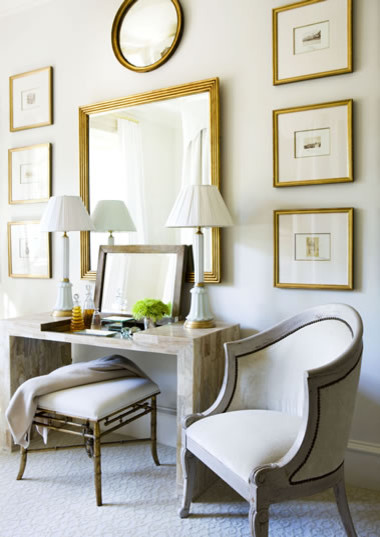 simple dressing table gold framed mirror gold framed wall decors light grey vanity chairs a couple of classic table lamps