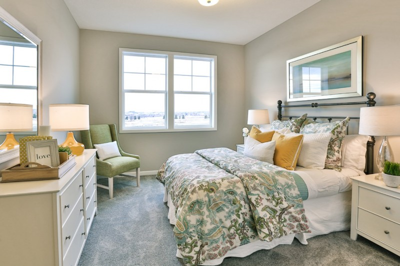 simple traditional bedroom classic metal bed frame with headboard grey comforter with classic motifs white hall console green corner chair grey walls with slide up glass windows