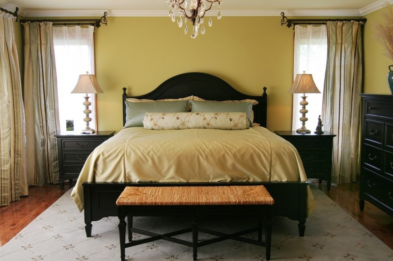 traditional and elegant bedroom idea mustard walls black stained window treatments black finished furniture and bed dark toned wood floors light blue carpet with motifs