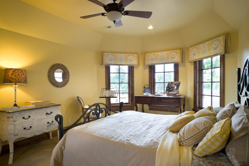 traditional bedroom concept pale mustard walls yellow pillowcases white bed linen wood framed windows with yellow upper skirts old wood hall table in classic style