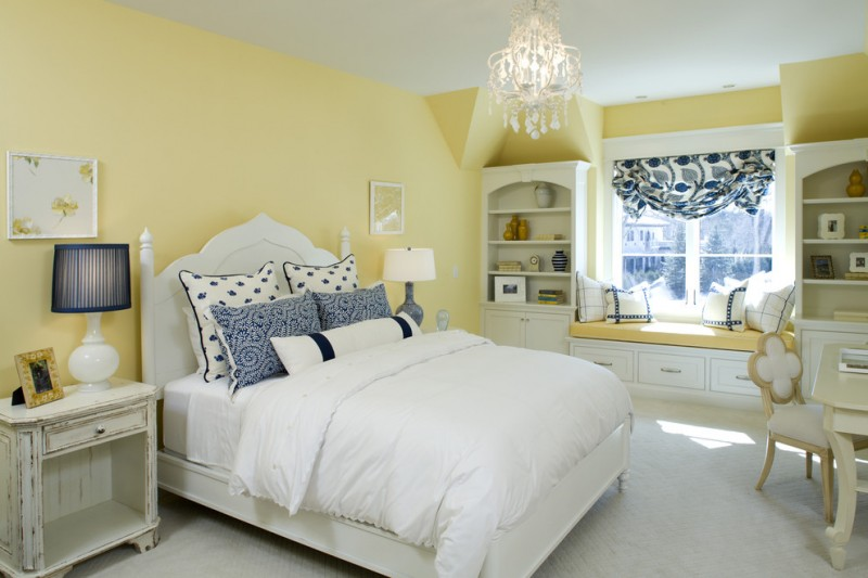 traditional bedroom soft mustard walls a couple of recessed storage units centered bench with mustard top and under storage white washed wood bedside tables
