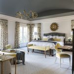 Traditional Master Bedroom Grey Bed Frame With Headboard White Walls Mustard Working Chair Mustard Settee Gold Toned Pendant Lamp Grey Painted Ceilings