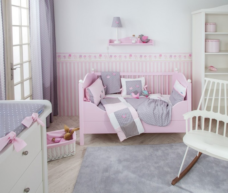 traditional nursery baby pink crib white rocking chair white changing table with grey mattress grey rug light wood floors light grey walls accented with stripped pink