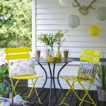 Traditional Porch Idea White Siding Exterior Walls Black Painted Wood Board Floors Bright Yellow Chairs Black Wrought Iron Table With Round Glass Top