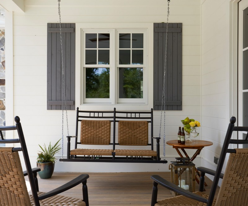traditional porch idea white siding exterior walls white trimmed exterior window with grey shutters hanging swing with black wrought iron structure small round top side table