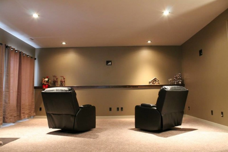 transitional basement idea recessed lamps a couple of black leather armchairs beige walls soft maroon window curtains