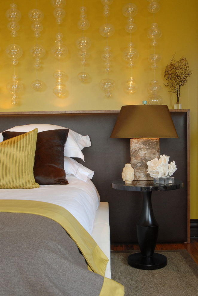 trendy & contemporary bedroom mustard yellow walls with glass bubbles with lighting inside large dark leather headboard white bed linen black finishing bedside table