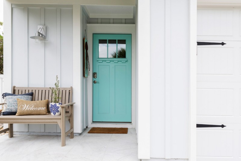 tropical themed front porch idea coastal blue front door with upper black glass soft wood bench with back multicolored accent pillows pale blue exterior walls white floors