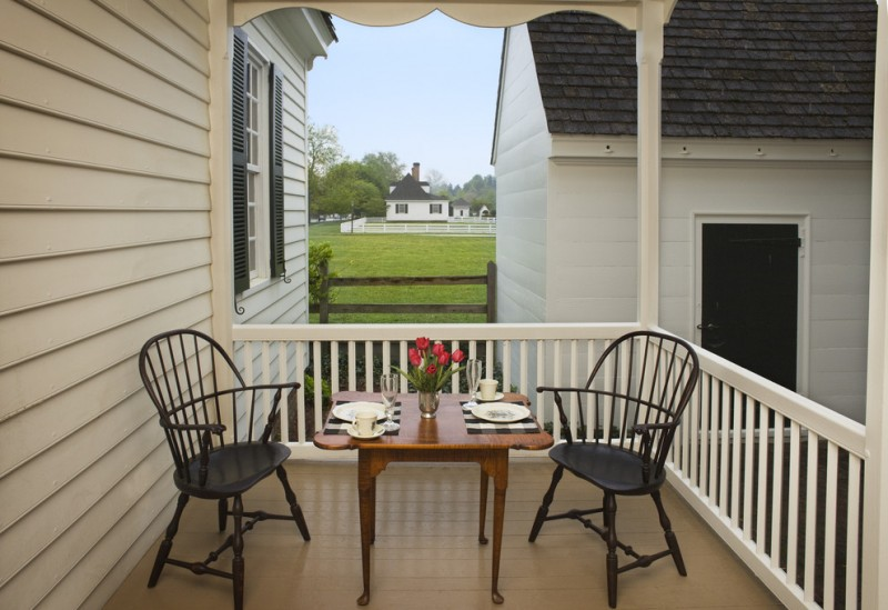 white deck and porch idea black finished chairs and dark toned wood center whire railing system white siding exterior walls