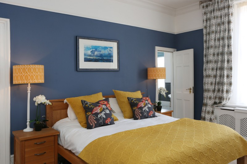 yellow mustard quilt with texture white bedding linen yellow mustard pillows dark pillows with floral motifs wood bed frame with headboard navy blue walls floor to ceiling drapery